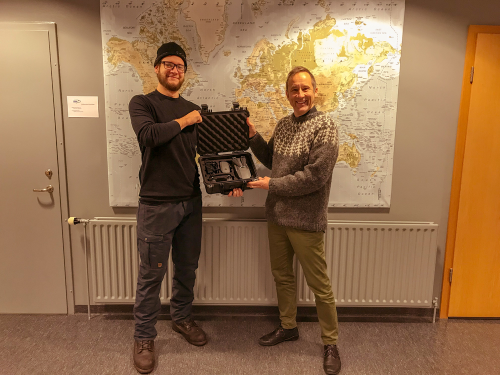 Justin Brown hands over the Mavic Air Pro drone to Peter Weiss the director of the University Centre.